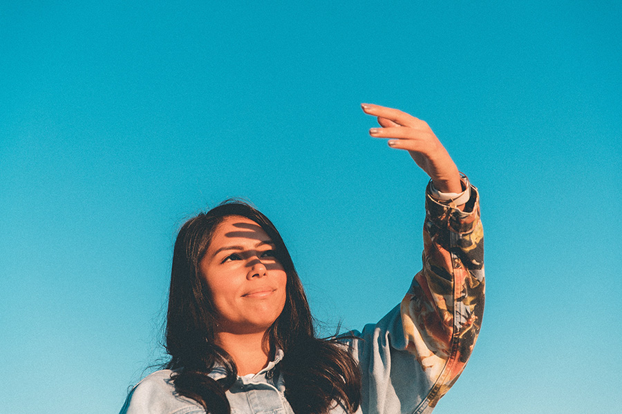 young woman, hand up and looking hopefully toward the sun
