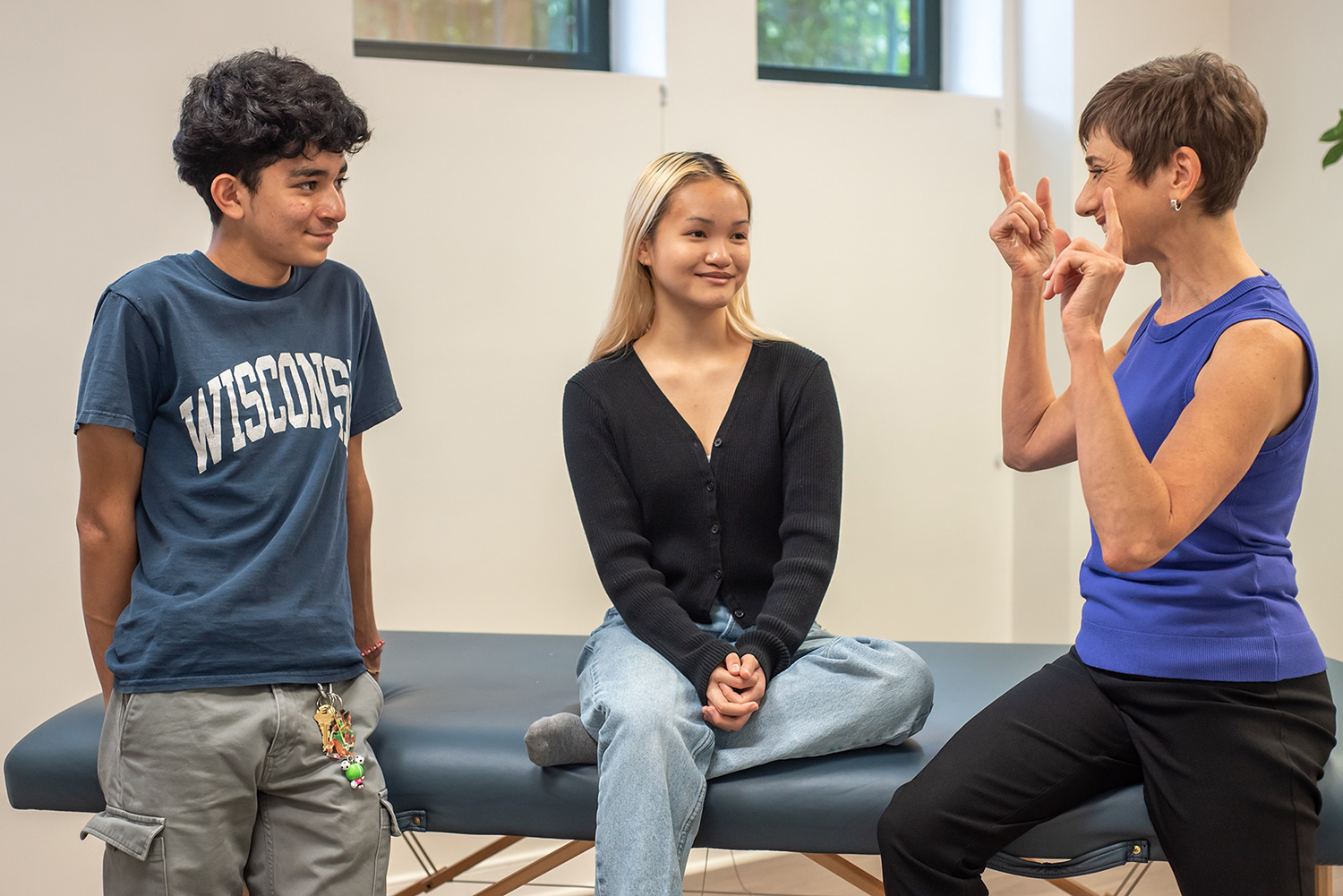 two teens working with Gabrielle in her therapy room