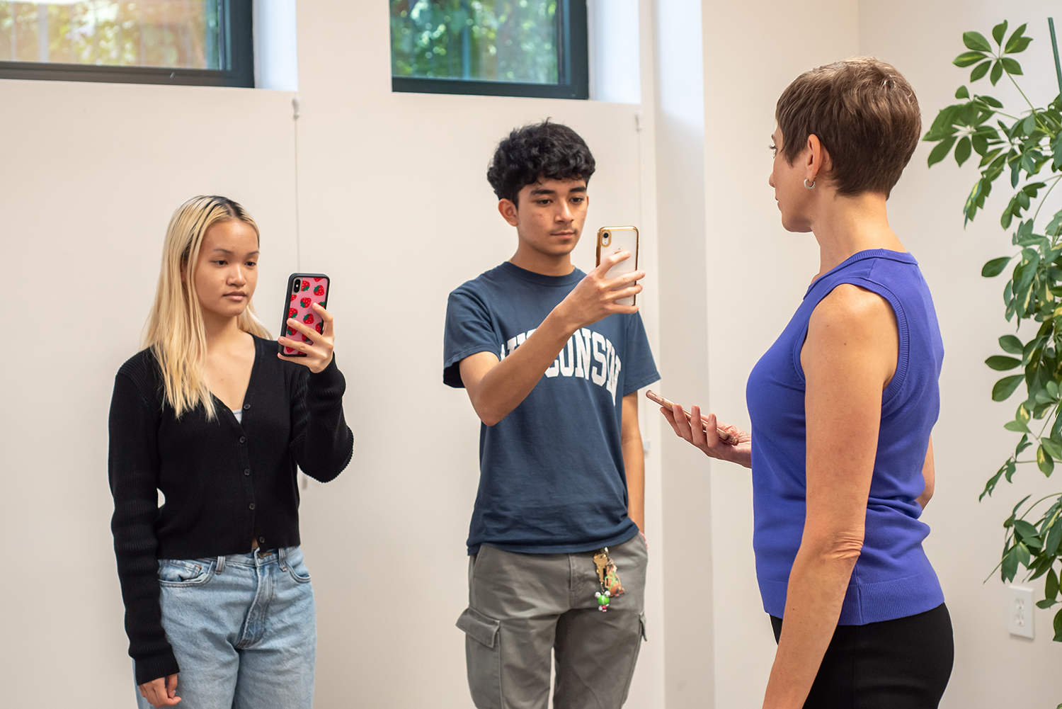 young adult teens with phones in their hands talking to gabrielle